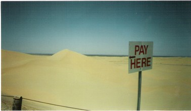 Photograph of a sign saying 'PAY HERE' in the middle of an empty desert