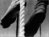 Black and white picture of two feet either side of a hung piece of rope Steve Dwoskin