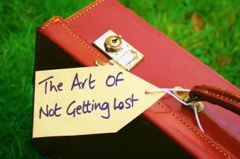 An old brown leather suitcase placed on grass with a luggage label which reads The Art Of Not Getting Lost