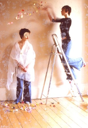 A woman on a step ladder scatters flowers on a masked woman standing below